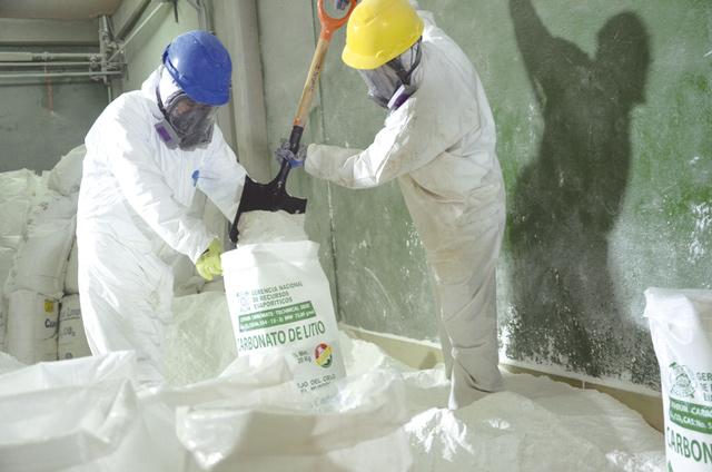 Arbeiter füllen in einer Pilotanlage im Salzsee von Uyuni in Bolivien Lithiumkarbonat in 20-Kilogramm-Säcke ein. Foto: Georg Ismar/dpa